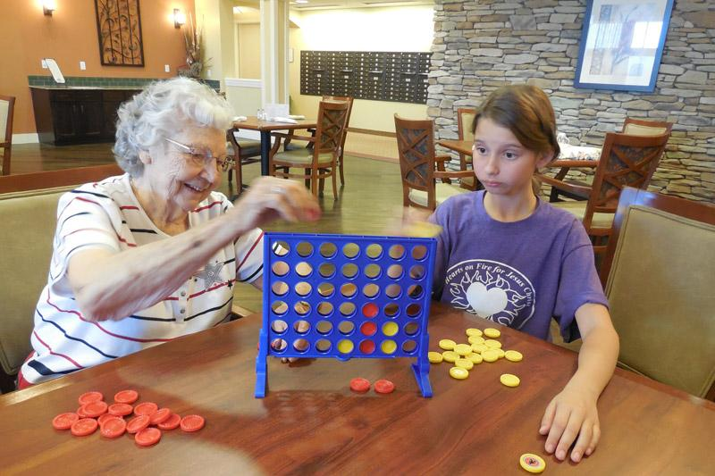 Resident and Child playing games at The Groves, A Merrill Gardens Community