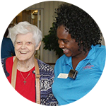 A resident and caregiver laugh together at Carriage Court of Hilliard in Hilliard