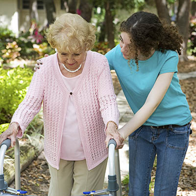 caretaker helping resident walk at Storey Oaks of Tulsa in Tulsa