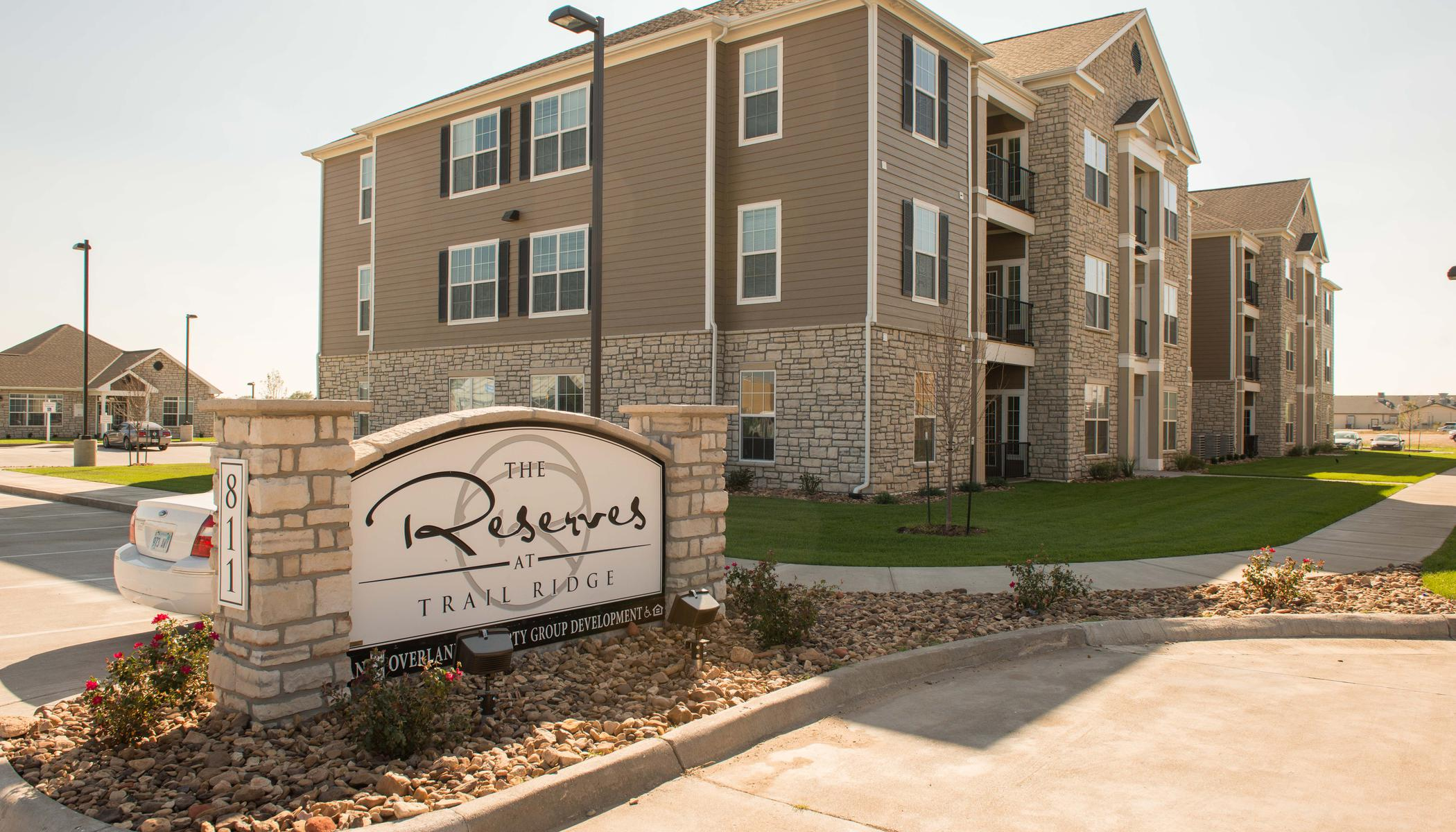 Exterior view of our apartments and main sign at The Reserves at Trail Ridge in Great Bend, KS
