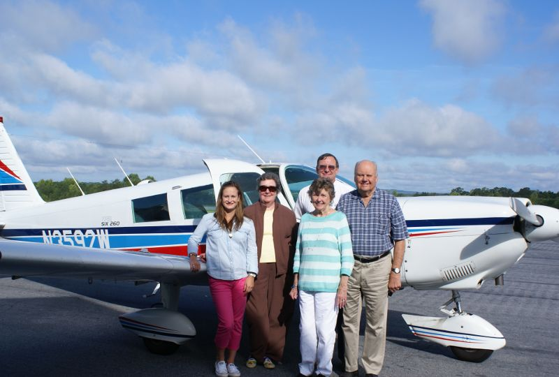 elder people posing in front of plane in activity at The Foothills Presbyterian Community in Easley, SC