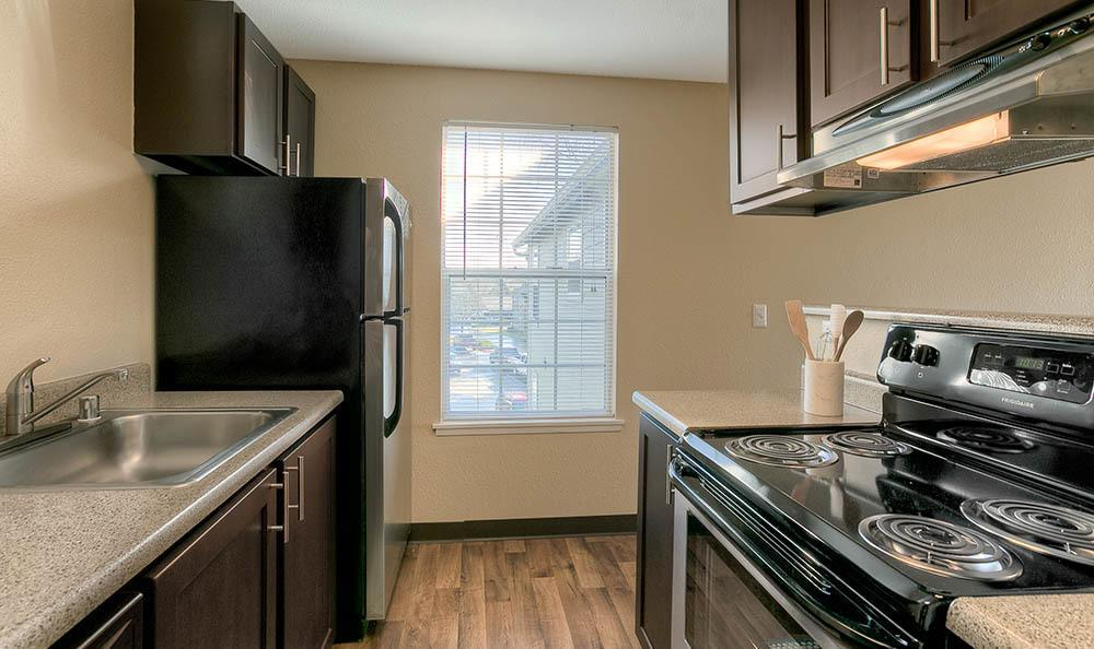 Kitchen With Hardwood Floors At Waters Edge Apartments