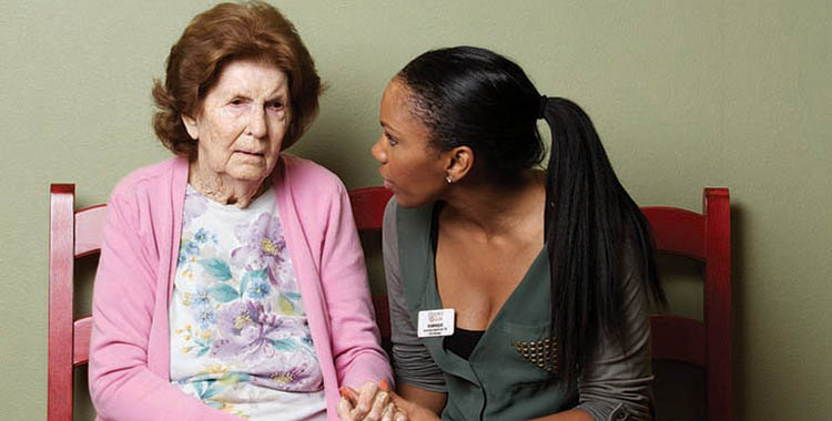 caretaker supporting a resident at Oxford Glen Memory Care at Carrollton