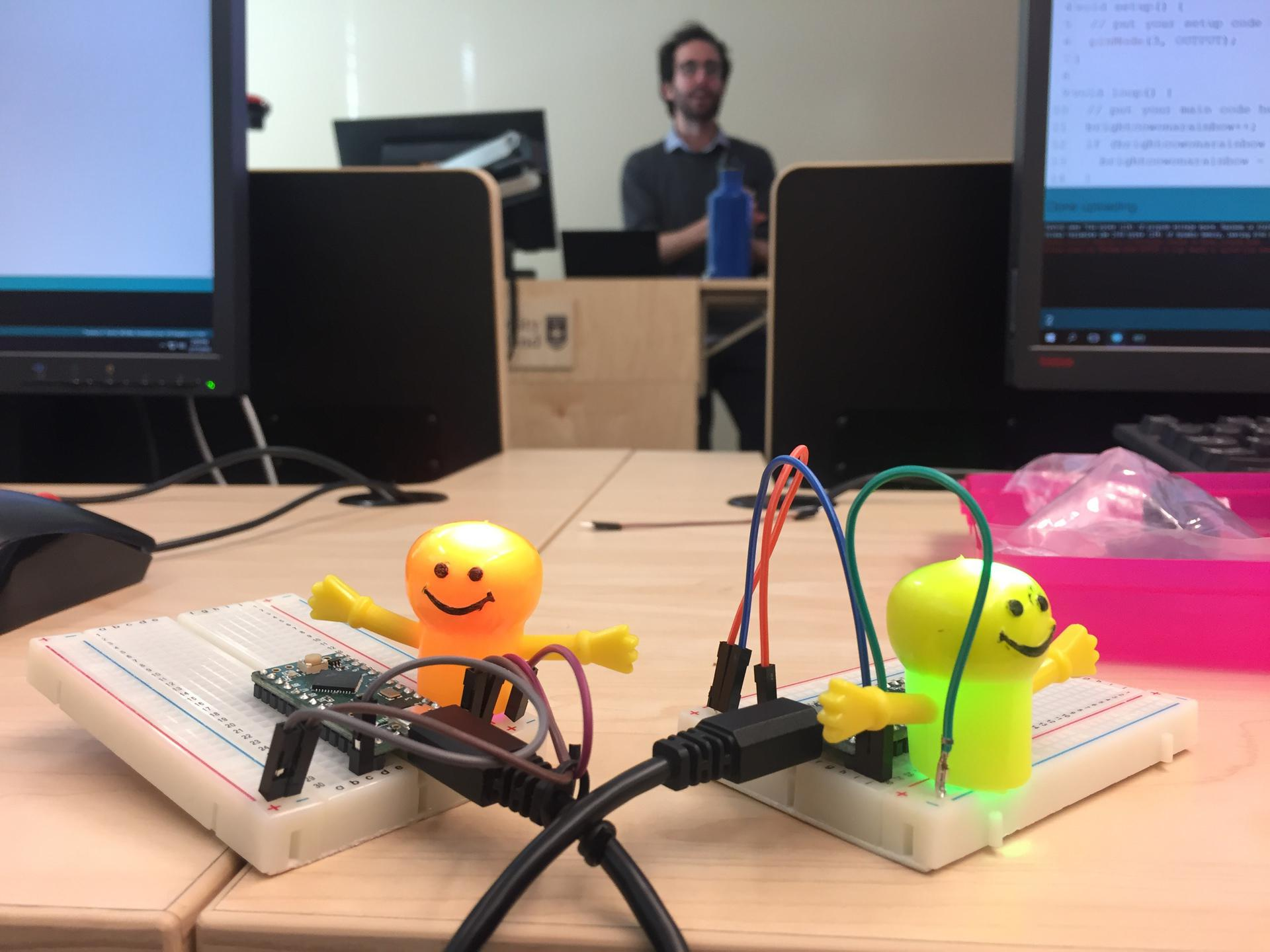 George Mandis teaching an Arduino class with cute little smiley-face finger puppets covering RGB LEDs