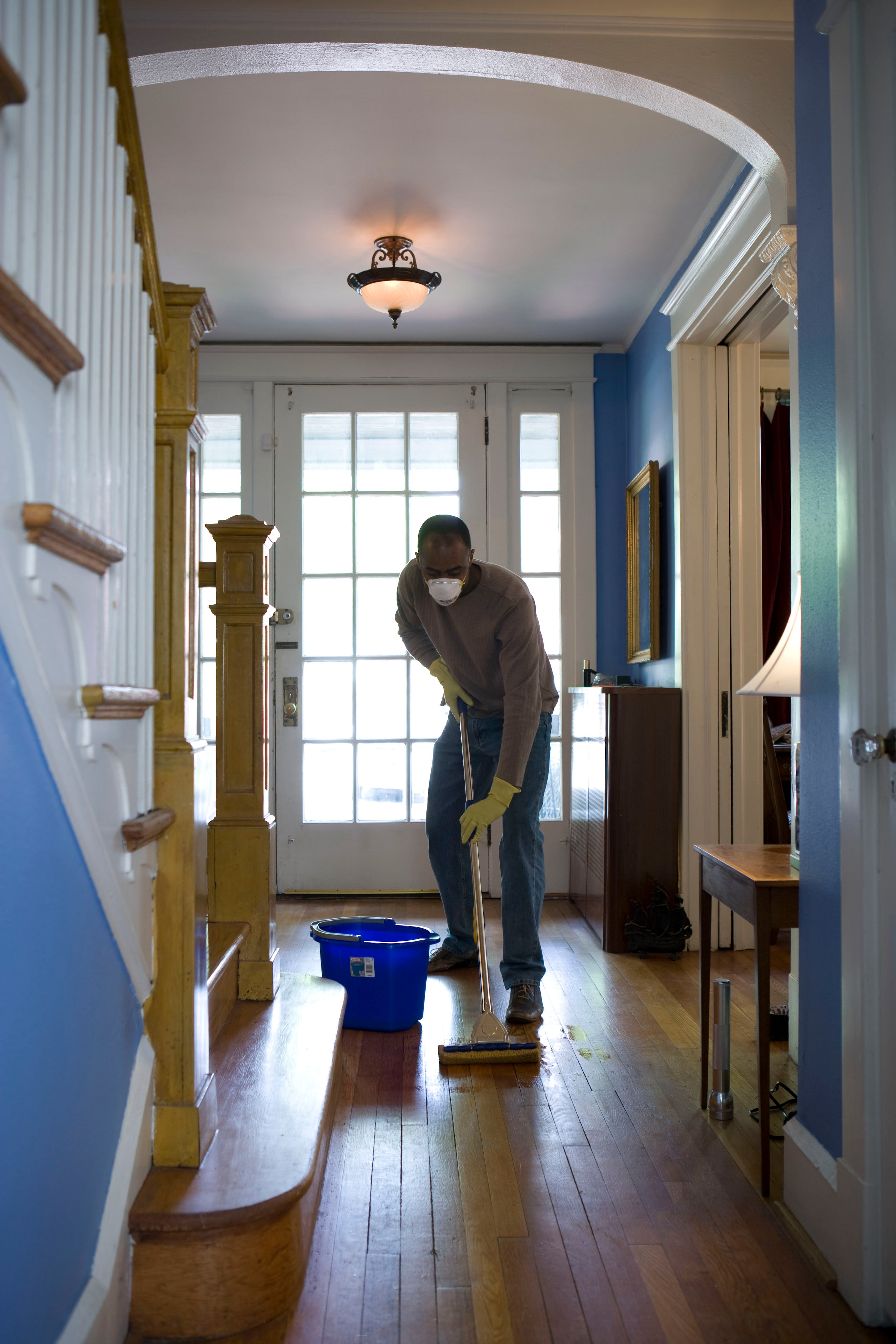 A Man Cleaning A Wooden Floor 2021618371