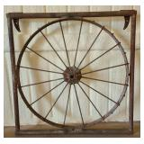 Vintage large heavy wagon wheel in an iron frame