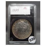 1884 Morgan silver dollar in Coin World holder.