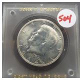 1964 Kennedy half dollar in plastic holder.