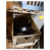 Crate of cast iron cookware