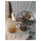 small metal fan and one vintage glass oil bottle