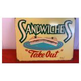 "Metal sign saying ""Sandwiches Take Out"""