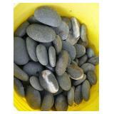 Bucket of small flat gray rocks