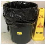 Large trash can and caution sign