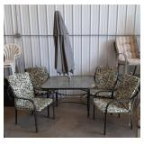 Patio dining set with 4 chairs and umbrella.