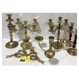 Lot of brass candelabra and candle holders.