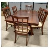 Wood dining room table with 6 padded seat chairs.