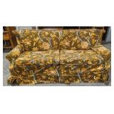 Sleeper couch with floral and bird cover. Cover