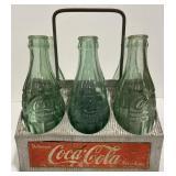 Vintage coca-cola bottles and metal pop carrier