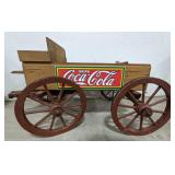Wooden wagon with Coca Cola sign on the side.