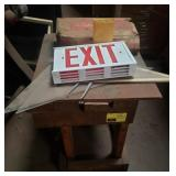 Wooden side table, exit sign, box of welding rods