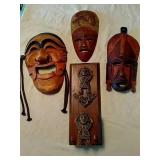 Collection of carved wooden masks and Indian wall