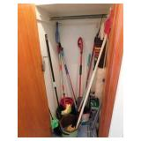Closet of cleaning supplies: mops - buckets -