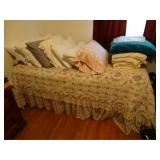 Twin bed with linens, pillows, blankets