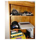 Top 3 shelves of book case, cables, brother