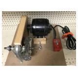 Motorized buffer mounted on wood plank.