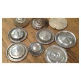 A lot of nine vintage automobile hubcaps