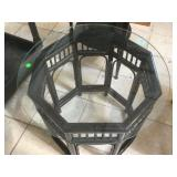 End table with black wooden stand and glass top.