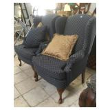 2 matching blue armchairs with wooden feet.
