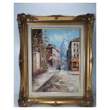 Cityscape painting in ornate frame