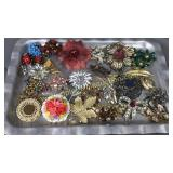 Vintage brooches and ear bobs on aluminum tray