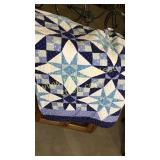 Hand done blue and white star quilt shows wear