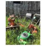 PILE OF LAWN MOWERS IN PIECES
