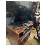 Flatscreen TVs DVD player and VHS on stand