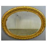 Oval gilt-framed mirror