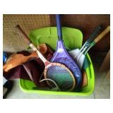 green tote of tennis raquets, bird feeders and