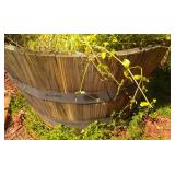 half wine barrell planter (by house inside fence)