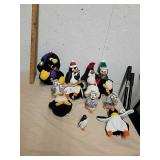 Group of stuffed penguin toys, ceramic figurines