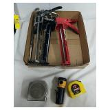Measure tapes caulking guns and flashlight
