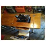 Singer brand sewing machine with table and chair.