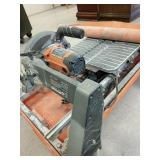 Rigid tile saw with roll out grid
