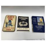 2 US Army books and a humorous wooden sign