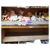 Shelf lot with different size dressed dolls