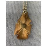 Fossilized bone pendant carved into a flower about