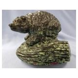 "Large stone carving of a bear on a log about 5"" ta"