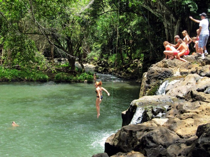 In a photo made July 6, 2011, a woman jumps into Kipu Falls in Lihue, Hawaii, on the island of Kauai.  But the alluring beauty of the waterfall and natural pool conceals a deadly side. Five visitors to Kauai, all male, have drowned at Kipu Falls in the past five years. (AP Photo/Audrey McAvoy)