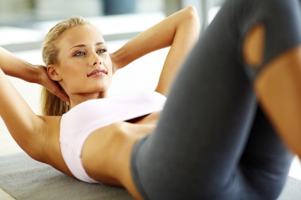 Portrait of a fit young female doing exercises for her abs